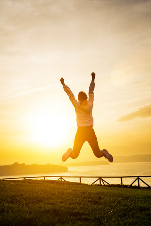 Happy sporty woman jumping and raising arms towards golden beautiful sunset and sea. Female athlete celebrating sport success and goals. Healthy lifestyle concept. Stockfoto
