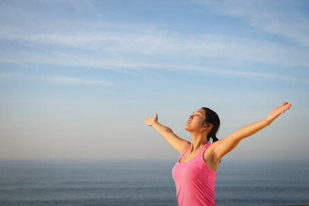 outstretching: Asian woman praising with arms raised to the sky by the sea. Relax and freedom concept.