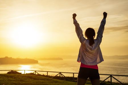 Successful sporty woman raising arms towards golden beautiful sunset and sea. Female athlete celebrating sport success and goals. Healthy lifestyle and freedom concept. Standard-Bild