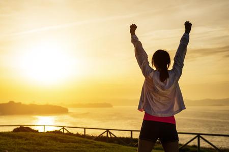 exito: Mujer deportiva acertada que levanta los brazos hacia hermosa puesta de sol y mar de oro. Atleta femenina celebrando el �xito y las metas deporte. Estilo de vida saludable y el concepto de la libertad.