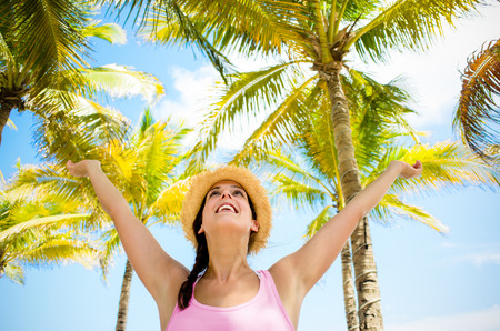 Blissful woman on tropical summer caribbean vacation raising arms to the sky with palm trees on background. Happy woman enjoying at the beach.