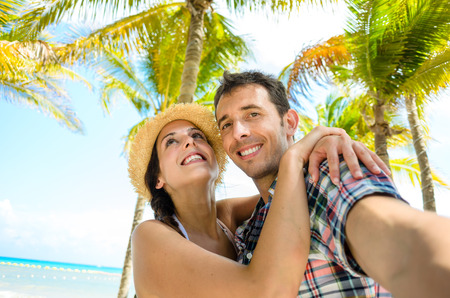 Couple on summer tropical vacation taking selfie photo on the beach. Man and woman on Mexico caribbean travel.