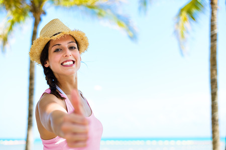 riviera maya: Summer caribbean vacation travel. Successful happy woman doing thumbs up approving gesture on beautiful palm trees and sea background.