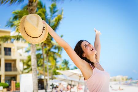 Relaxed cheerful woman enjoying tropical caribbean vacation at the beach in Playa del Carmen, Riviera Maya, Mexico.