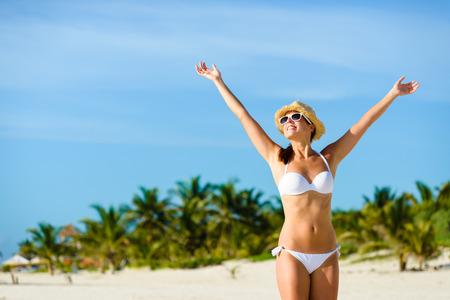 Mooie zalige vrouw in bikini genieten van tropisch strand en Caraïbische zomervakantie. Gelooid brunette verhogen armen en genieten van de vrijheid door de zee bij Playa Paraiso, Riviera Maya, Mexico.