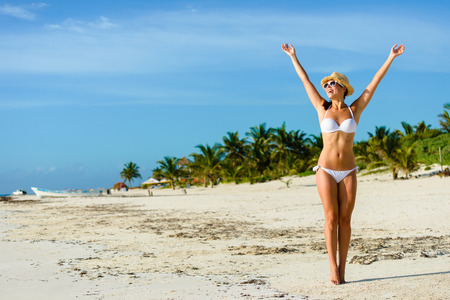 Beautiful blissful woman in white bikini enjoying tropical beach and caribbean summer vacation. Tanned brunette raising arms and enjoying freedom by the sea at Playa Paraiso, Riviera Maya, Mexico.