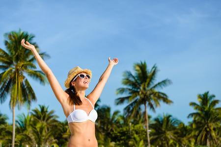 riviera maya: Happy blissful woman in white bikini enjoying tropical beach and caribbean summer vacation. Tanned brunette raising arms and enjoying freedom in Playa Paraiso, Riviera Maya, Mexico.