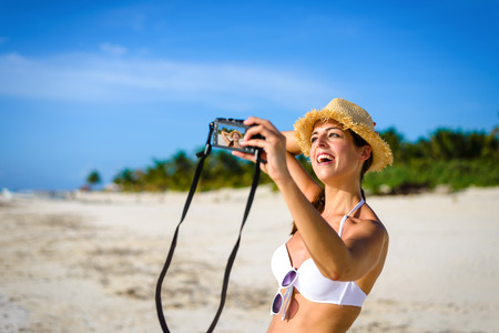 riviera maya: Joyful woman taking selfie photo on tropical caribbean vacation. Happy brunette having fun in Playa Paraiso, Riviera Maya, Mexico.