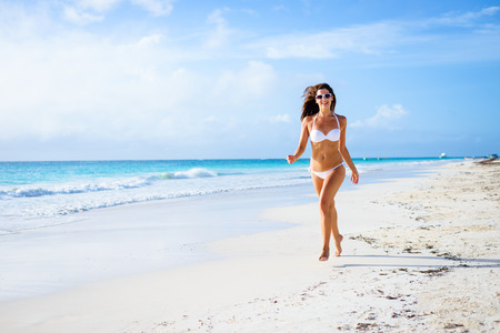 Beautiful joyful woman in white bikini enjoying tropical beach and caribbean summer vacation. Tanned brunette running and enjoying freedom by the sea at Playa Paraiso, Riviera Maya, Mexico. Stock Photo
