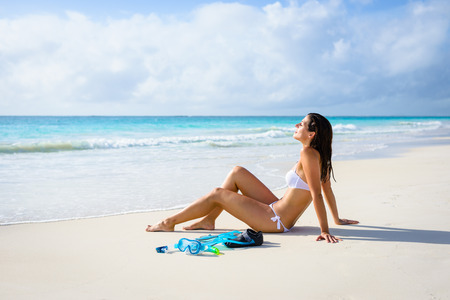 Relaxed woman on tropical beach vacation enjoying tranquility and resting after snorkeling. Brunette beautiful girl in white bikini relaxing and sunbathing.