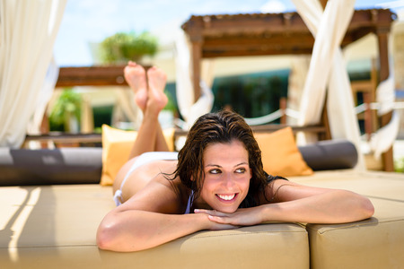 longue: Young woman relaxing on outdoor chaise longue at resort poolside. Brunette caucasian girl in white bikini enjoying summer vacation for resting and relax.
