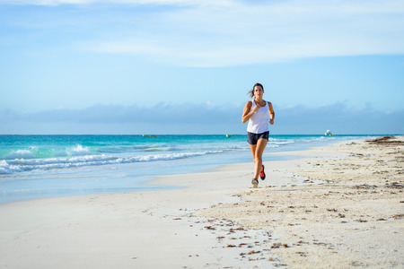 Sporty woman running by the sea on tropical beach during caribbean vacation. Fitness and healthy lifestyle on summer holidays.