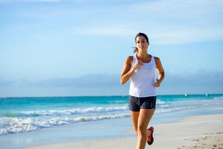 corriendo: Mujer deportiva que se ejecuta junto al mar en la playa tropical durante las vacaciones del Caribe. Fitness y estilo de vida saludable para sus vacaciones de verano.
