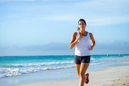 Sporty woman running by the sea on tropical beach during caribbean vacation. Fitness and healthy lifestyle on summer holidays. Zdjęcie Seryjne - 36978688