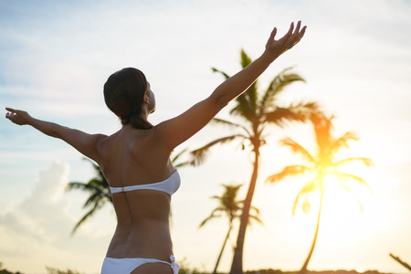 blissful: Blissful woman enjoying freedom and happiness on caribbean tropical vacation. Caucasian brunette raising arms towards the sunset and palm trees.