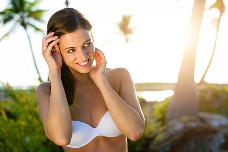 beautiful smile: Brunette young woman in bikini on tropical caribbean vacation. Caucasian model at natural virgin beach in Riviera Maya, Mexico. Stock Photo