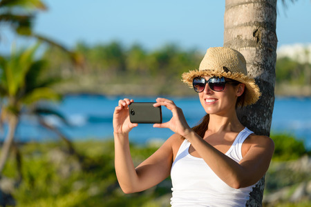riviera maya: Woman on caribbean tropical vacation taking photos with smartphone camera. Brunette tourist on travel to Riviera Maya, Mexico.