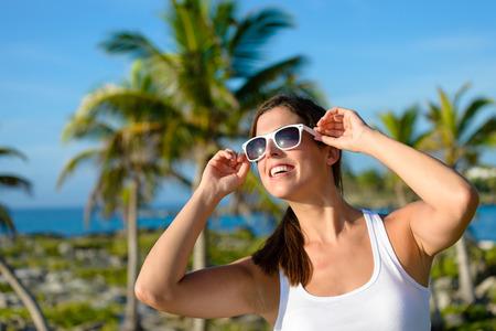 riviera maya: Woman enjoying caribbean vacation travel. Caucasian brunette wearing sunglasses towards palm trees. Stock Photo