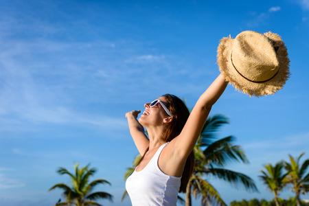 하늘 열대 카리브해 휴가 모금 팔 행복한 여자. 자유와 여행 개념. 여름 휴가를 즐기는 갈색 머리 여자. 스톡 콘텐츠