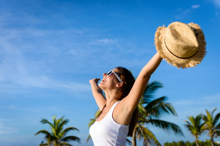 Blissful woman on tropical caribbean vacation raising arms to the sky. Freedom and travel concept. Brunette woman enjoying summer holidays. Stock Photo