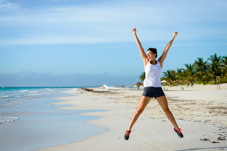 Joyful woman celebrating running and sport success. Female athlete jumping at tropical beach. Sport goals concept.