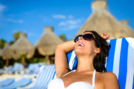mayan riviera: Joyful woman at tropical resort caribbean beach resting on outdoor chaise lounge. Summertime vacation tourism and travel concept. Beautiful brunette sunbathing and relaxing at Mayan Riviera, Mexico.