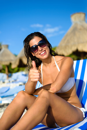 mayan riviera: Joyful woman at tropical resort caribbean beach doing thumbs up success gesture. Summertime vacation tourism and travel concept. Beautiful brunette sunbathing and relaxing at Mayan Riviera, Mexico.