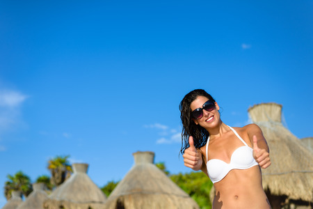 mayan riviera: Joyful woman at tropical resort caribbean beach doing thumbs up success gesturing. Summertime vacation tourism and travel concept. Beautiful brunette sunbathing and relaxing at Mayan Riviera, Mexico.