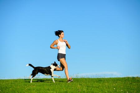 Vrouw en hond lopen en uitoefening van buiten op het gras veld in de zomer of voorjaar. Gelukkig vrouwelijke atleet training met haar huisdier.