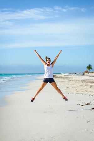 Joyful woman celebrating running and sport success. Female athlete jumping at tropical beach. Sport goals concept.