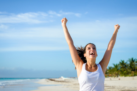 Sporty woman running and raising arms at tropical beach. Sport success concept. Female athlete training and ejoying outdoor workout.