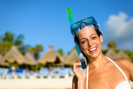 mayan: Happy woman on caribbean tropical travel and vacation wearing snorkel gear. Cheerful brunette enjoying sport sea activity on resort beach. Mayan Riviera, Mexico.