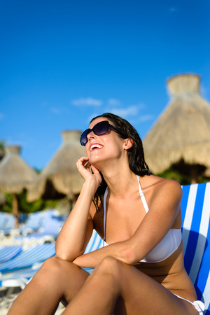 mayan riviera: Joyful woman at tropical resort caribbean beach looking up to the blue sky. Summertime vacation tourism and travel concept. Beautiful brunette sunbathing and relaxing at Mayan Riviera, Mexico.