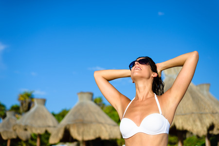 mayan riviera: Blissful woman at tropical resort caribbean beach enjoying freedom and leisure. Summertime vacation tourism and travel concept. Beautiful brunette sunbathing and relaxing at Mayan Riviera, Mexico. Stock Photo
