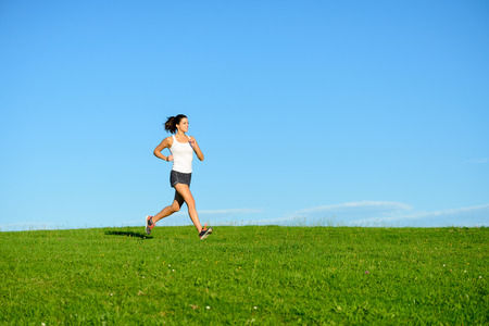 spring training: Woman running on summer or spring grass field. Female athlete exercising outdoor. Brunette fit sporty model training towards clear blue sky background.