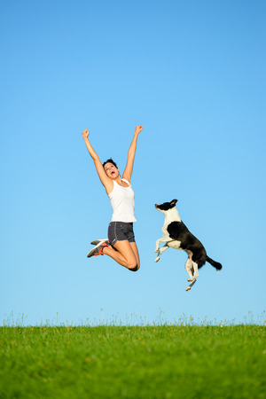 Joyful sporty woman and dog jumping and having fun after running and exercising outdoor together. Female athlete and her pet celebrating sport success and freedom. Standard-Bild