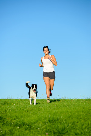spring training: Woman and dog running and exercising outdoor in grass field on summer or spring. Happy female athlete training with her pet. Stock Photo