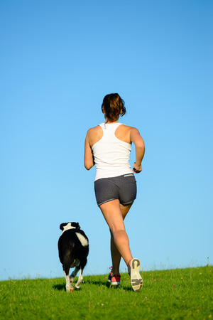 spring training: Sporty woman and dog running and training together outdoor at park on summer or spring. Female athlete exercising with her pet. Stock Photo