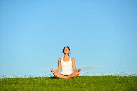 Młoda kobieta robi joga ćwiczenia relaksujące i oddychając świeżym powietrzu. Relaks i spokój na zielonym polu trawy w kierunku błękitne niebo jasne.