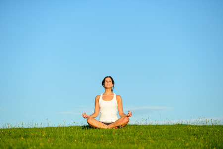 Mujer joven que hace yoga relajante y respiración ejercicio al aire libre. Relax y tranquilidad en el campo de hierba verde hacia el cielo azul claro.