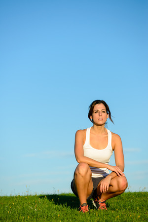 crouched: Sporty woman taking a workout rest. Motivated female athlete on a running break for breathing. Motivation and healthy lifestyle concept.