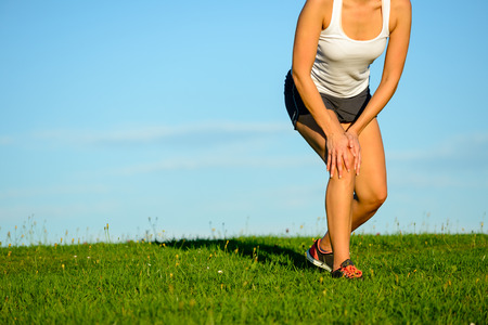 contracture: Sport running knee injury. Sportswoman touching painful leg after exercising off road on grass field. Athlete runner training accident.