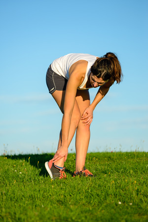 sprain: Sport running ankle sprain. Sportswoman touching painful twisted or broken ankle after exercising off road on grass field. Athlete runner training accident. Stock Photo