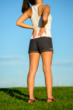 back training: Female athlete suffering lower back pain during outdoor running or exercising. Woman with sport injury.