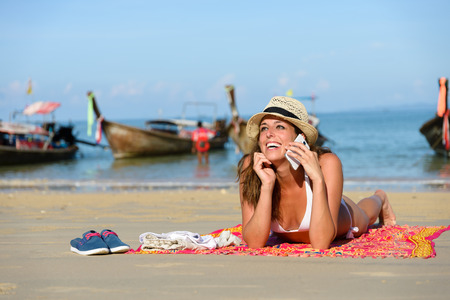 Woman enjoying travel beach vacation in Krabi, Thailand. Happy young brunette sunbathing  and talking on smartphone at Railay Beach.
