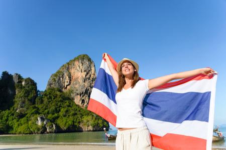 brunette woman: Happy woman having fun at Krabi beach with Thailand flag. Beautiful brunette enjoying travel to Asia.