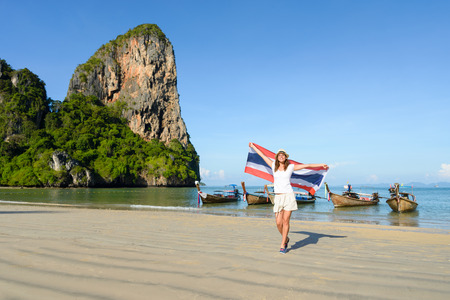 Happy woman having fun at Krabi beach with Thailand flag. Beautiful brunette enjoying travel to Asia.