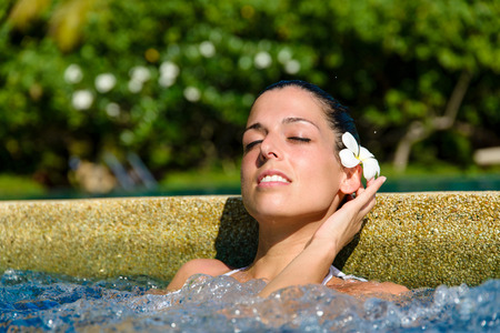 relax: Beautiful relaxed woman enjoying spa pool at resort in Thailand. Relaxing outdoor jacuzzi. Stock Photo
