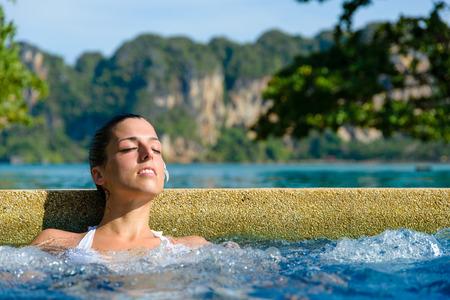 relajado: Mujer relajada hermosa que disfruta de piscina de hidromasaje en el centro tur�stico en Tailandia. Relajante jacuzzi al aire libre. Foto de archivo