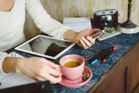 Working at home concept. Entrepeneur business woman checking email or messaging on smartphone and drinking coffee. Stock Photo - 41069994